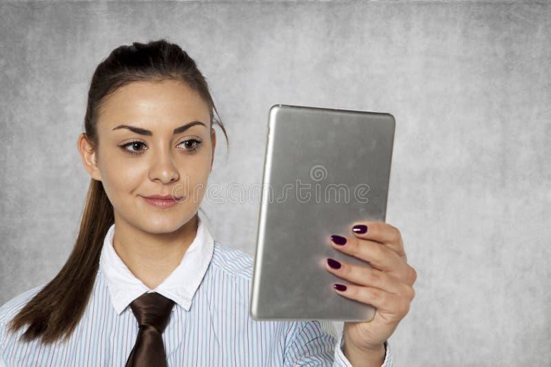 Affärskvinnan läser i stillhet på informationen på internet honom royaltyfri foto