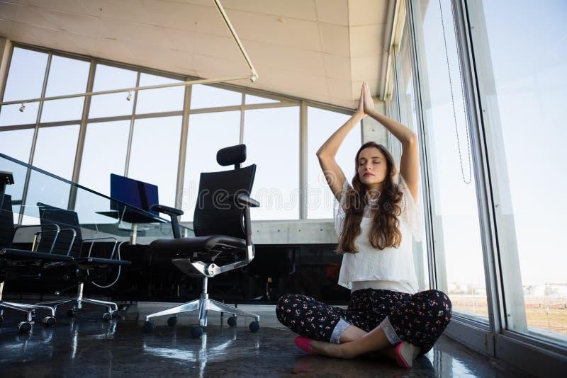 Affärskvinnan med ögon stängde att göra yoga på golv arkivbilder