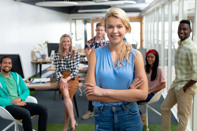 Affärskvinnan med armar korsade att se kameran medan olika kollegor som står i bakgrund fotografering för bildbyråer