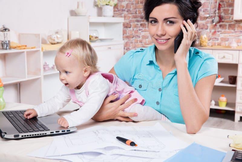 Affärskvinnan med bärbara datorn och hennes behandla som ett barn flickan royaltyfri bild