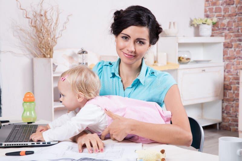Affärskvinnan med bärbara datorn och hennes behandla som ett barn flickan arkivfoto