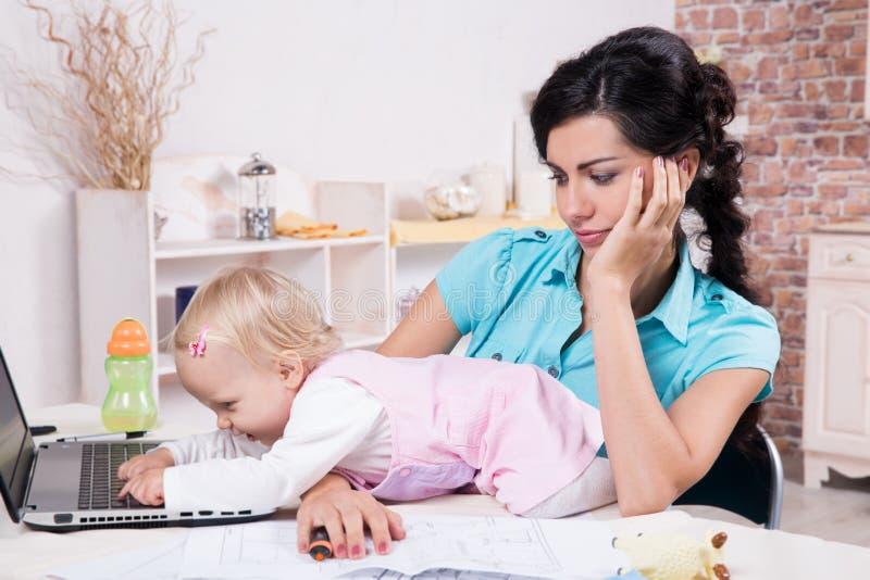 Affärskvinnan med bärbara datorn och hennes behandla som ett barn flickan arkivbild
