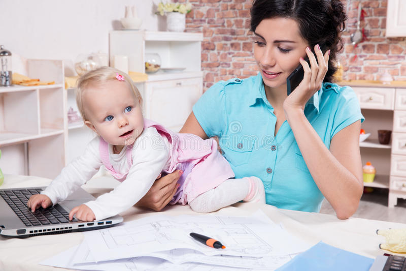 Affärskvinnan med bärbara datorn och hennes behandla som ett barn flickan arkivbilder