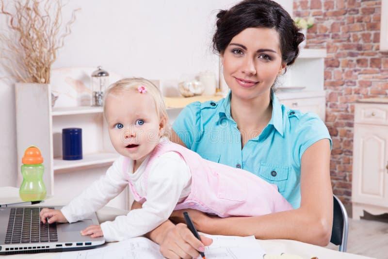 Affärskvinnan med bärbara datorn och hennes behandla som ett barn flickan arkivfoton