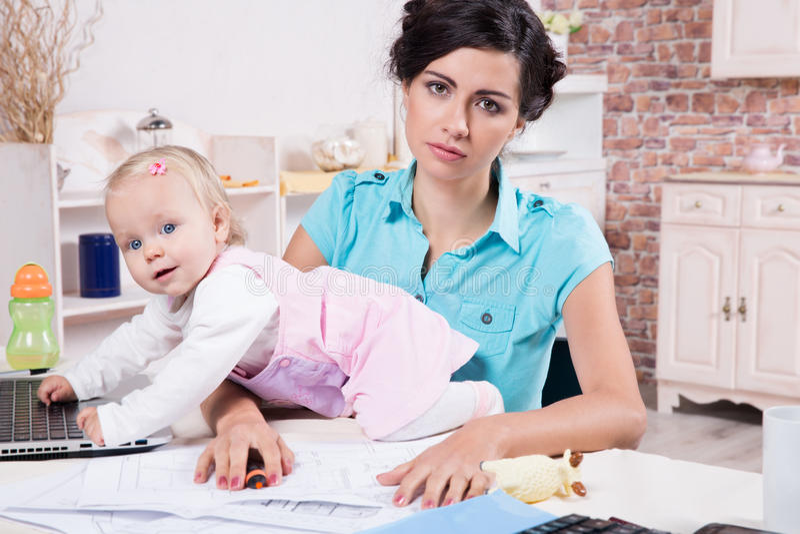 Affärskvinnan med bärbara datorn och hennes behandla som ett barn flickan royaltyfria foton