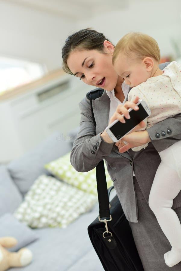 Affärskvinnan med behandla som ett barn och smartphonen som sent får för arbete royaltyfri fotografi