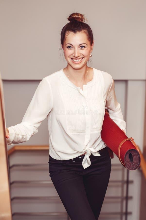 Affärskvinnan med blåa ögon i den vita blusskjortan och svart flåsar matt hållande bärande yoga i regeringsställning arkivfoton