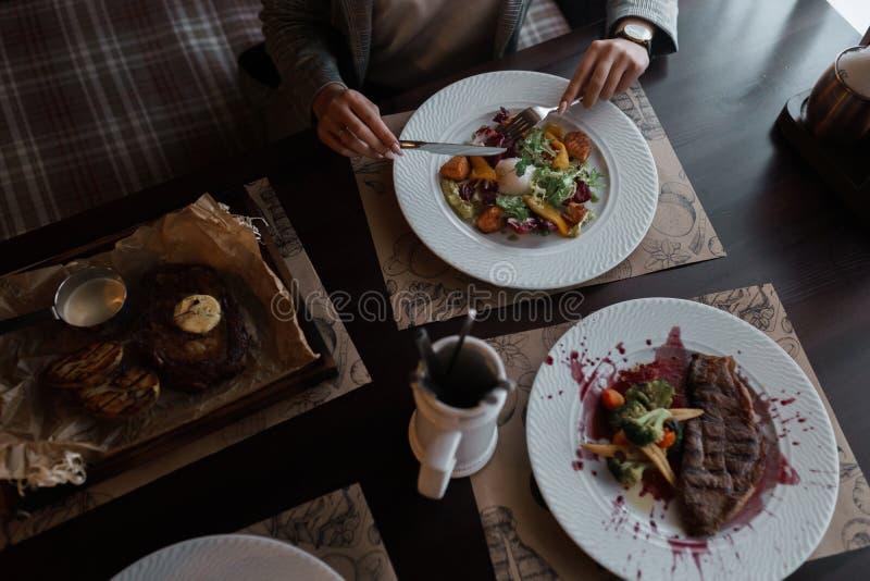 Affärskvinnan med en kniv och en gaffel äter en grönsaksallad från nya grönsaker med fisken och det tjuvjagade ägget i ett kafé arkivbilder