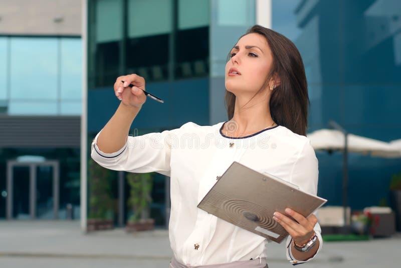 Affärskvinnan med en mapp i hennes hand vägleder processen royaltyfria bilder