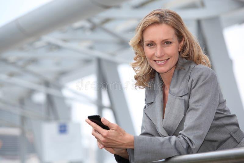 Affärskvinnan med mobil ringer royaltyfri bild