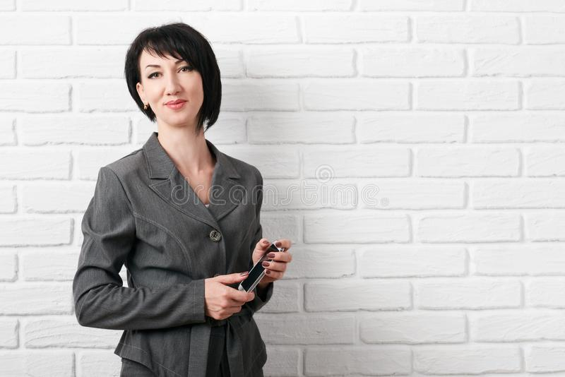 Affärskvinnan med smartphonen som är iklädd en grå dräkt, poserar framme av en vit vägg arkivfoto