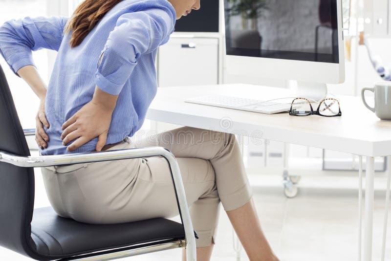 Affärskvinnan med tillbaka smärtar i regeringsställning royaltyfria foton