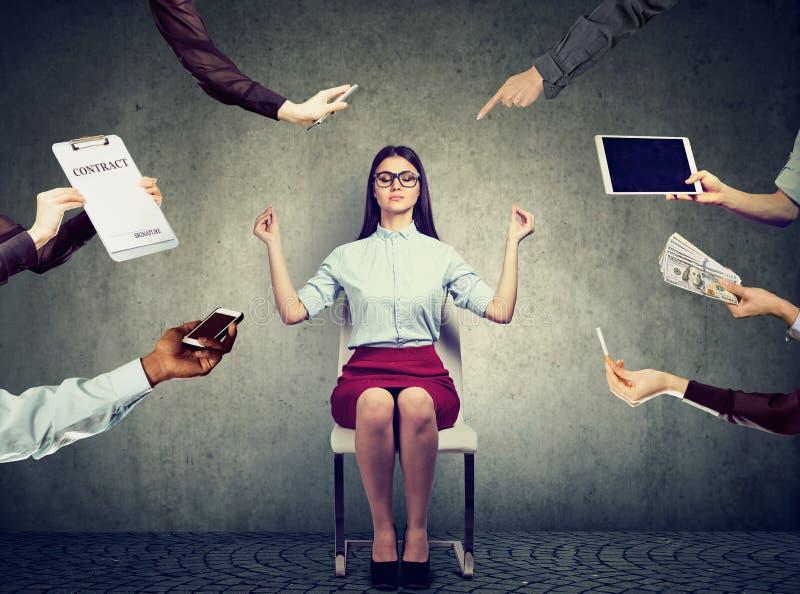 Affärskvinnan mediterar för att avlösa spänning av upptaget företags liv arkivbilder