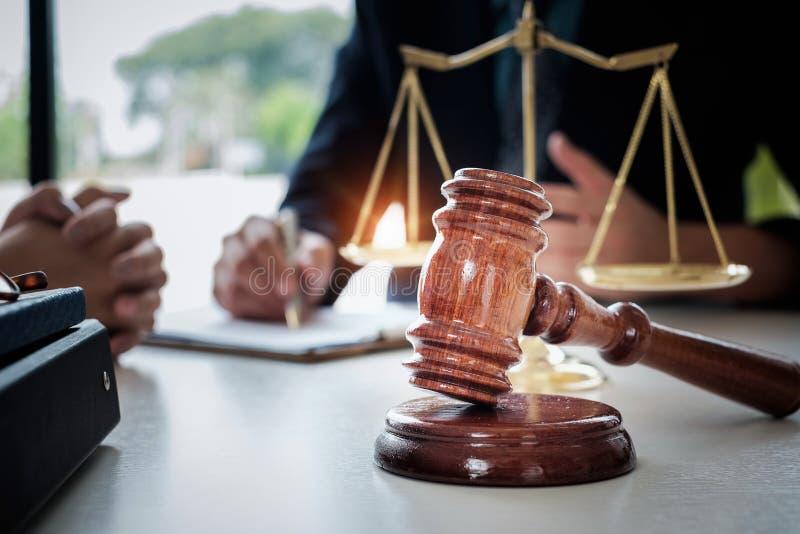Affärskvinnan och advokater som diskuterar avtalet, skyler över brister med mässingsskalan på träskrivbordet i regeringsställning arkivbild