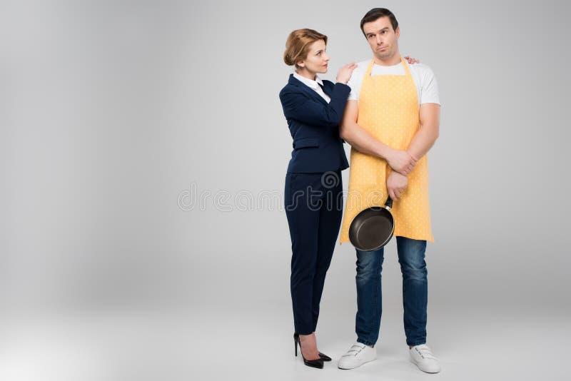 affärskvinnan och mannen förargar husägaren med stekpannan som tillsammans kramar feminismbegrepp royaltyfri fotografi
