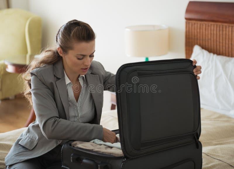 Affärskvinnan packar upp bagage i hotellrum royaltyfri fotografi