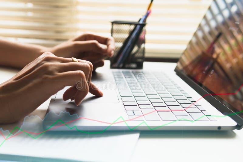 Affärskvinnan räcker den upptagna användande bärbara datorn på kontorsskrivbordet royaltyfri bild