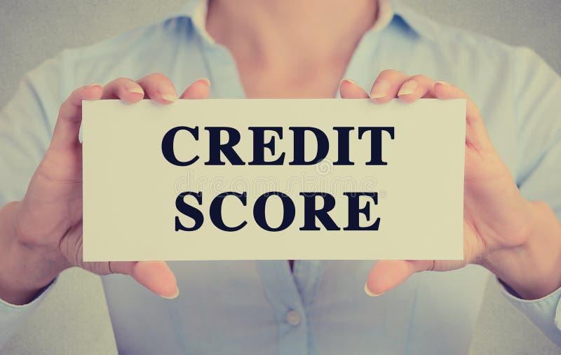 Affärskvinnan räcker det hållande korttecknet med meddelandet för text för krediteringsställningen arkivbild