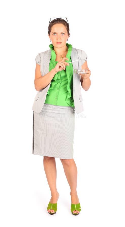 Affärskvinnan rymmer askfatet och röker i studio arkivfoto