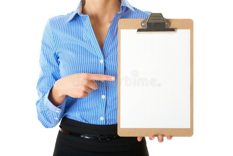 Affärskvinnan rymmer clipboarden och punkt till den royaltyfri fotografi