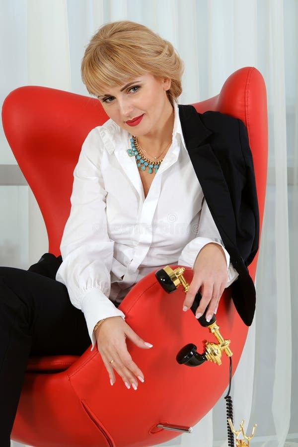Affärskvinnan rymmer telefontelefonluren royaltyfria foton