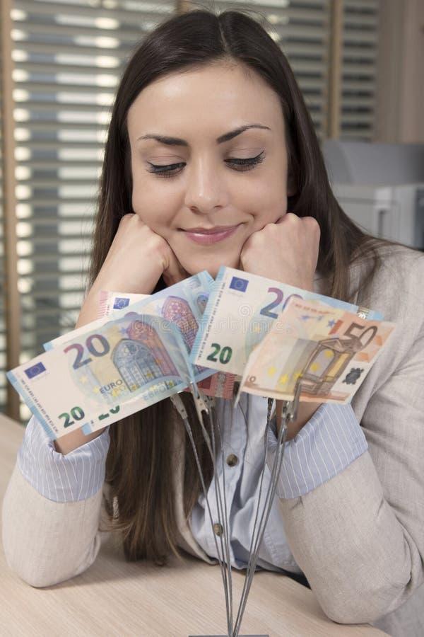 Affärskvinnan ser ett träd som göras av pengar royaltyfri bild