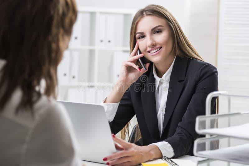 Affärskvinnan ser kameran Hennes kollega ser arkivbilder