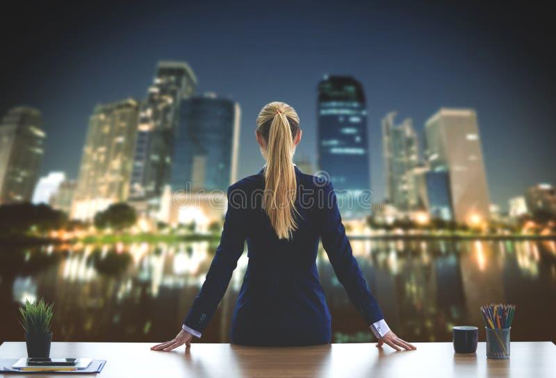 Affärskvinnan ser ut fönstren för framgång royaltyfri fotografi