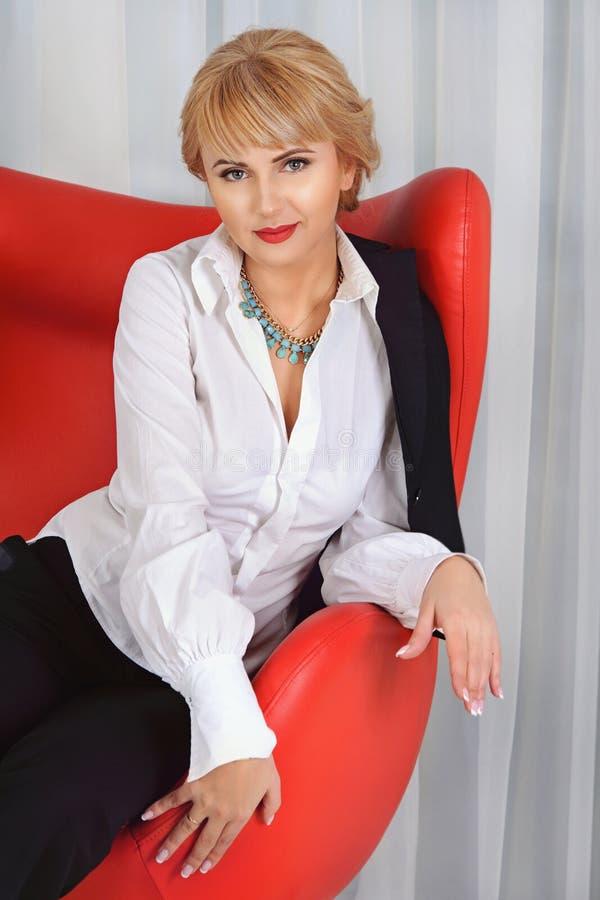 Affärskvinnan sitter i en röd stol arkivbild