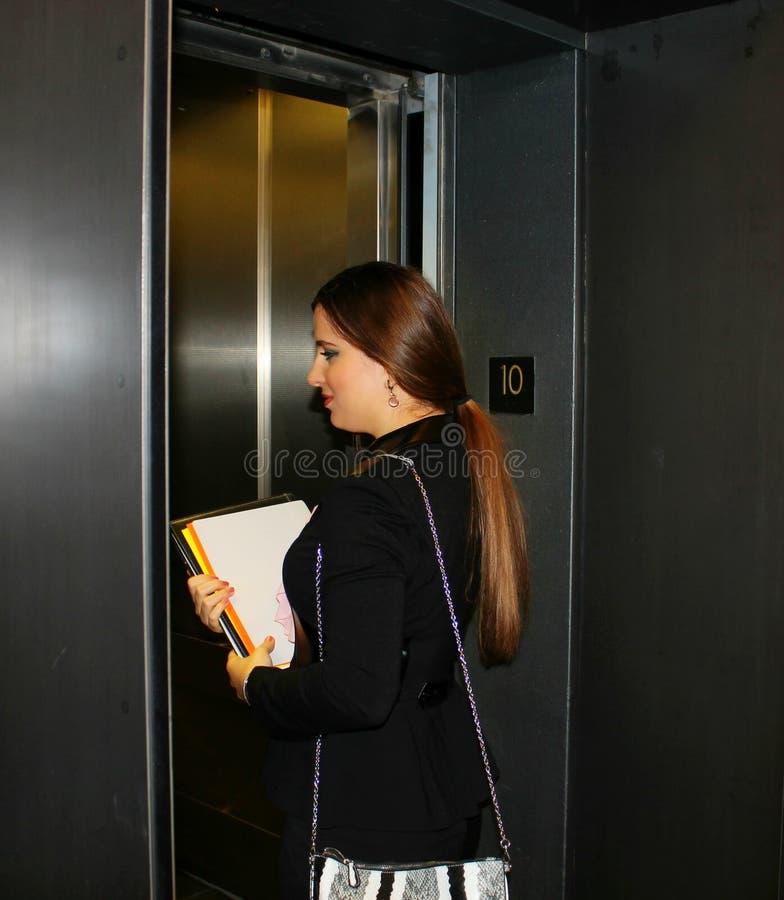 Affärskvinnan skriver in hissen royaltyfri foto