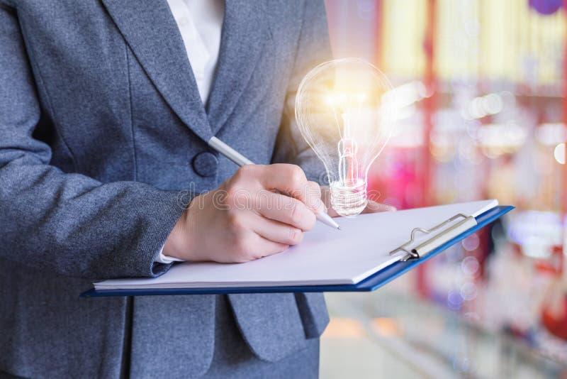 Affärskvinnan skriver ner idéer i en kontrolllista royaltyfri bild