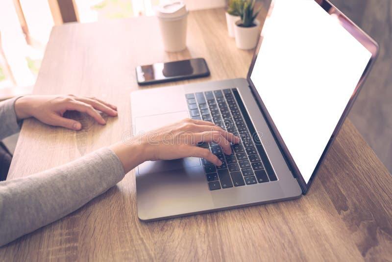 Affärskvinnan som använder bärbar datordatoren, gör online-aktivitet på hemmastatt kontor för trätabell royaltyfri fotografi