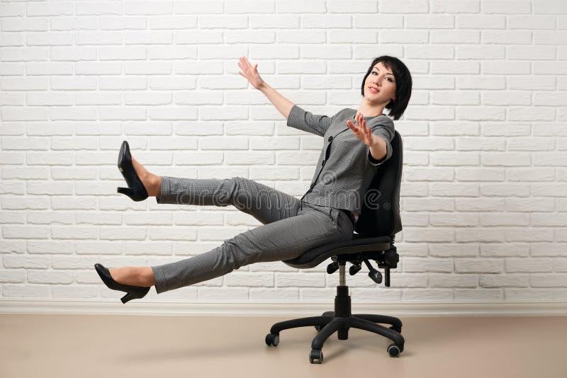 Affärskvinnan som har gyckel, nedgångar från stol som är iklädd en grå dräkt, poserar framme av en vit vägg royaltyfria foton