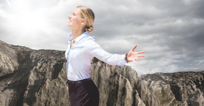 Affärskvinnan som tycker om solen mot, vaggar och molnig himmel arkivbilder