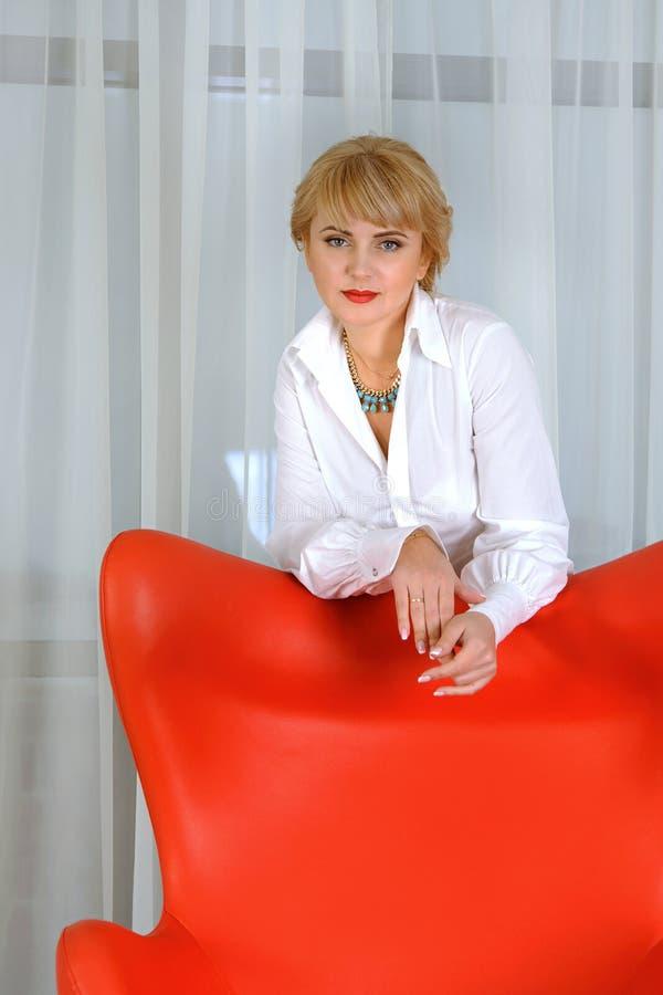 Affärskvinnan står bak den röda stolen royaltyfri bild