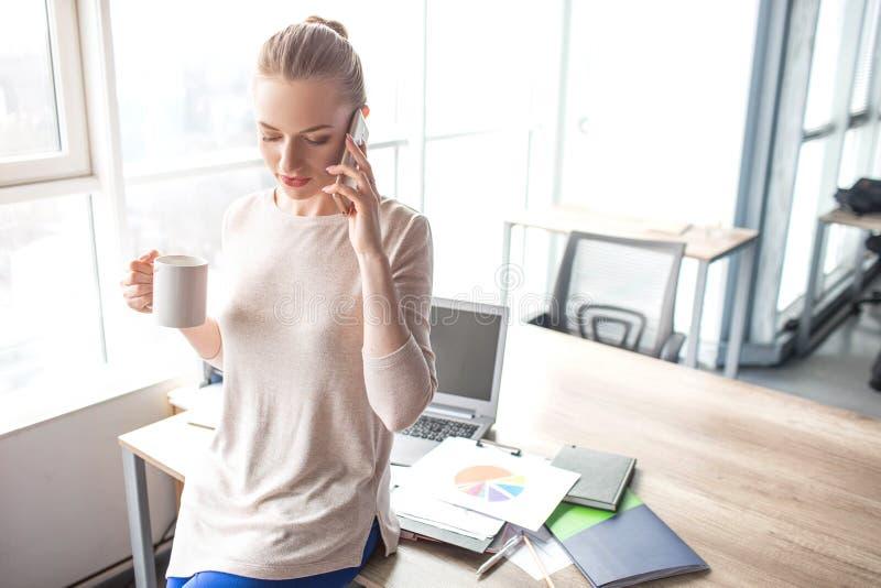 Affärskvinnan står på hennes kontorstabell och talar på telefonen Hon rymmer en kopp te i en hand och arkivfoto