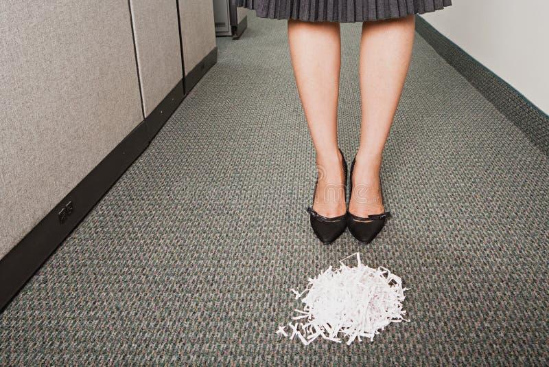 Affärskvinnan stod framme av högen av pappers- shreddings arkivbilder