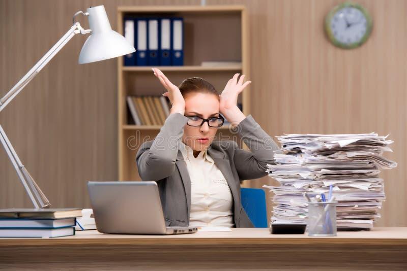 Affärskvinnan under spänning från för mycket arbete i kontoret arkivbild