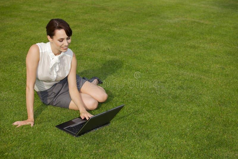 Affärskvinnan Using Laptop At parkerar royaltyfri bild