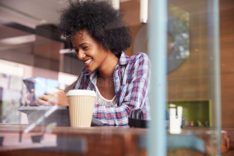 AffärskvinnaOn Phone Using Digital minnestavla i coffee shop fotografering för bildbyråer