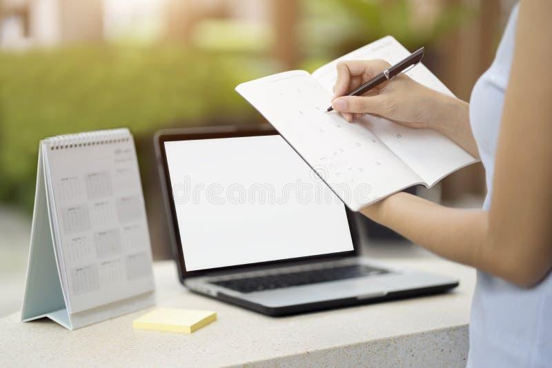 Affärskvinnaplanläggningsdagordning och schema genom att använda kalenderhändelse royaltyfria bilder