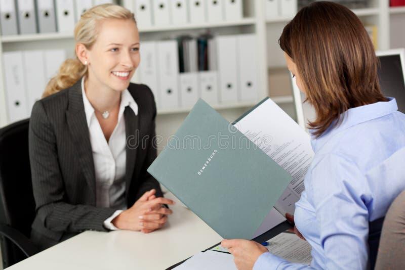 AffärskvinnaReadings Female Candidates CV på skrivbordet fotografering för bildbyråer