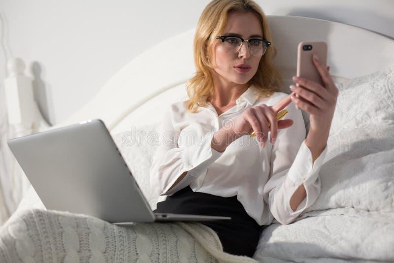 Affärskvinnasammanträde i säng, genom att använda bärbara datorn royaltyfri foto