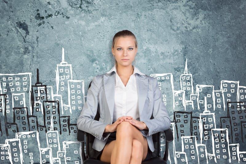 Affärskvinnasammanträde mot väggen med skissar av royaltyfria foton