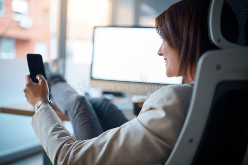 Affärskvinnasammanträde och användamobiltelefon på arbetsplatsen in av arkivbild