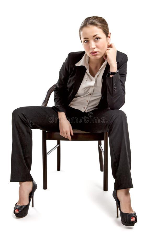 Affärskvinnasammanträde på en stol på vit royaltyfri fotografi