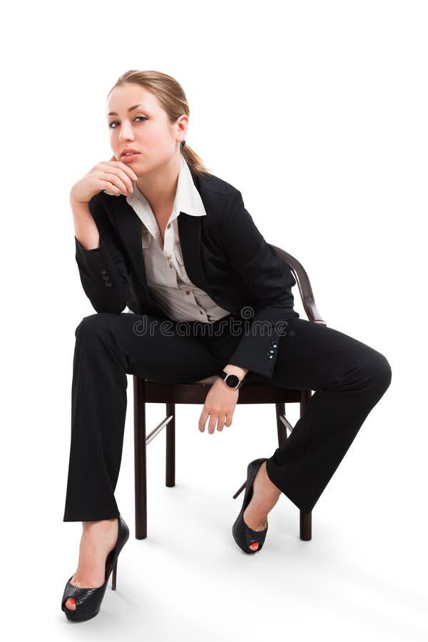 Affärskvinnasammanträde på en stol som isoleras på vit royaltyfri fotografi