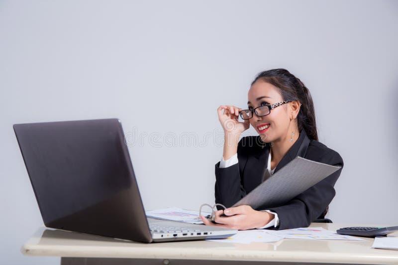 Affärskvinnasammanträde på hållande exponeringsglas för skrivbord och för hand i regeringsställning royaltyfria foton