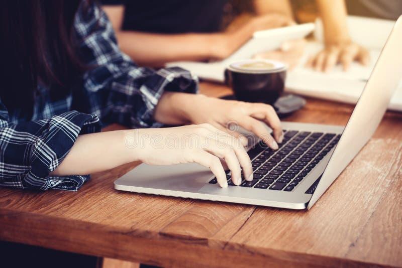 Affärskvinnasammanträde på kontorsskrivbordet och maskinskrivning på en bärbar dator räcker tätt upp, den anonyma framsidan royaltyfri foto