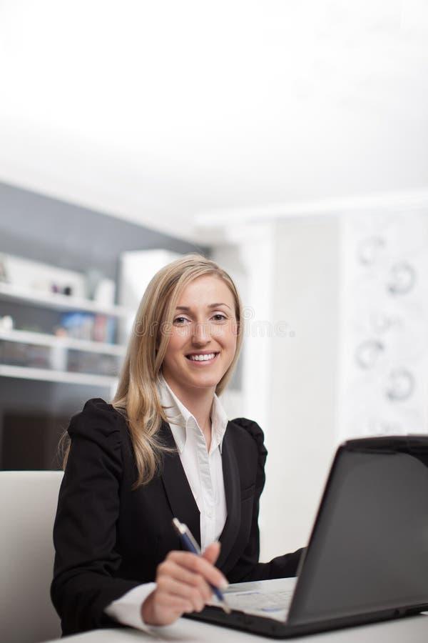 Affärskvinnasammanträde som arbetar på hennes bärbar dator royaltyfri fotografi
